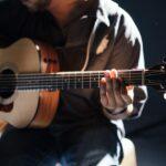 Guitarist strummer en akkord i et mørkt lokale