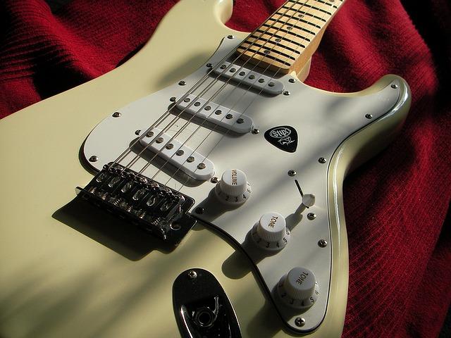 Et billede af en hvid Fender Stratocaster med single coil pickups og et sort plektre på slagpladen.